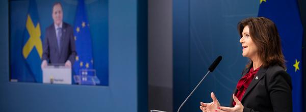 Statsminister Stefan Löfven på skärm och arbetsmarknadsminister Eva Nordmark i en talarstol på pressträff.
