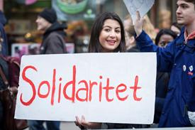 Syntolkning av bild: En leende tjej håller i ett plakat med texten Solidaritet. Hon befinner sig i ett demonstrationståg. Foto från Partistyrelsens bildarkiv.